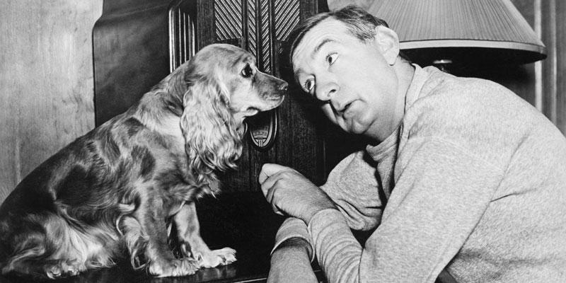 Foto em preto e branco de um Cachorro e um Homem se olhando